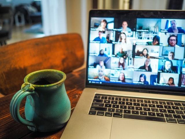 Das Bild zeigt eine Tasse und einen Laptop, auf dem eine Videokonferenz läuft.